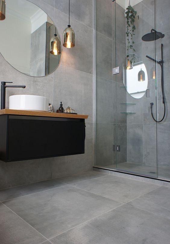 Banheiro moderno revestido todo de cimento queimado, luminárias pendentes e balcão da pia preto com detalhe de madeira