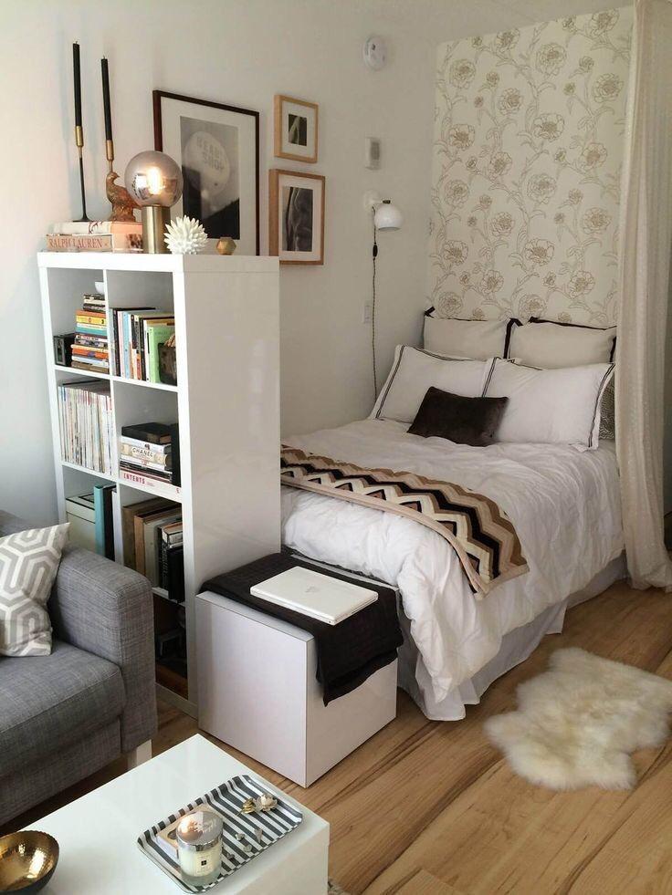 decoração para quartos pequenos de casal com armário dividindo ambiente, papel de parede floral e piso de madeira.
