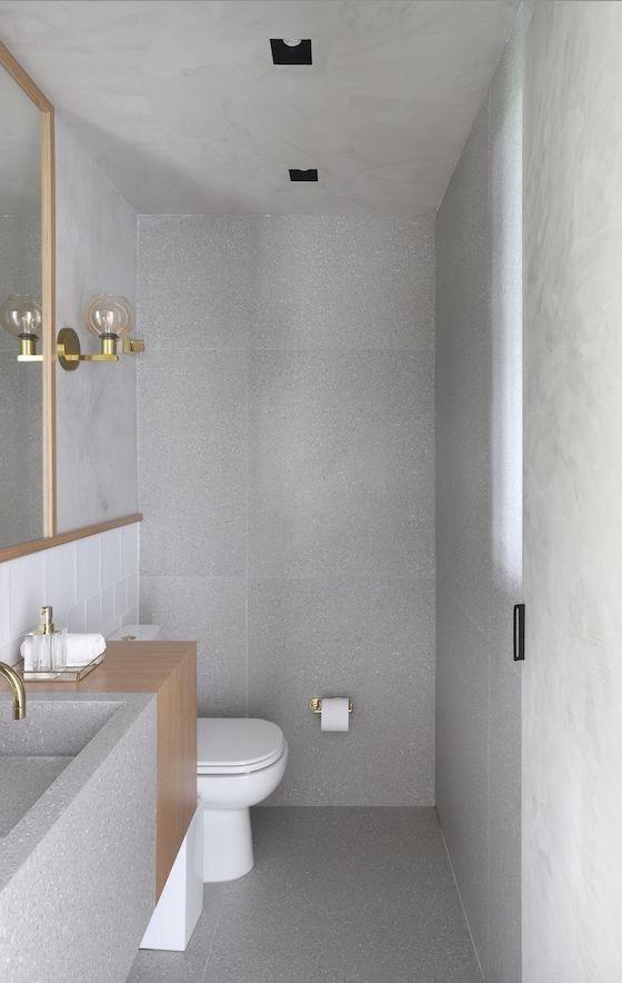 Banheiro moderno todo revestido de cimento queimado, dando um aspecto de profundidade