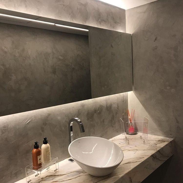 Lavabo moderno revestido de cimento queimado com pia branca, e espelho amplo