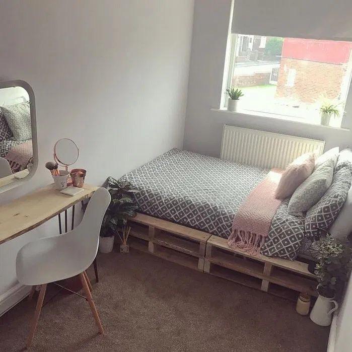 decoração para quartos pequenos com cama de pallet, carpete no chão, paredes brancas, bancada de madeira e cadeira branca.