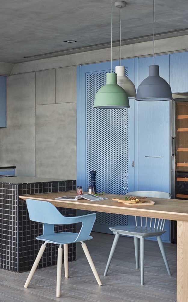 Ambiente com chão revestido de cimento queimado, com detalhes em azul na decoração