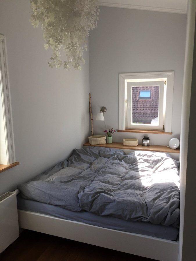 decoração para quartos de casal pequenos com iluminação natural, detalhes em madeira e planta branca pendente.