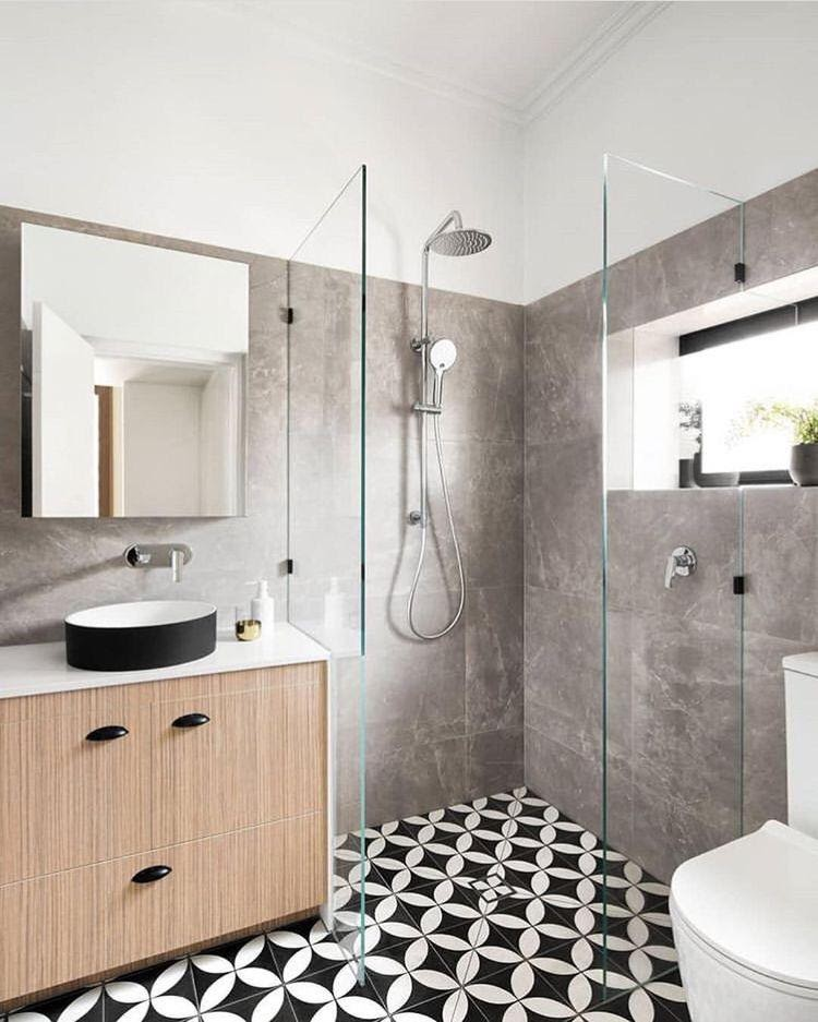 Banheiro moderno com paredes revestidas de cimento queimado, armário de madeira e box de vidro