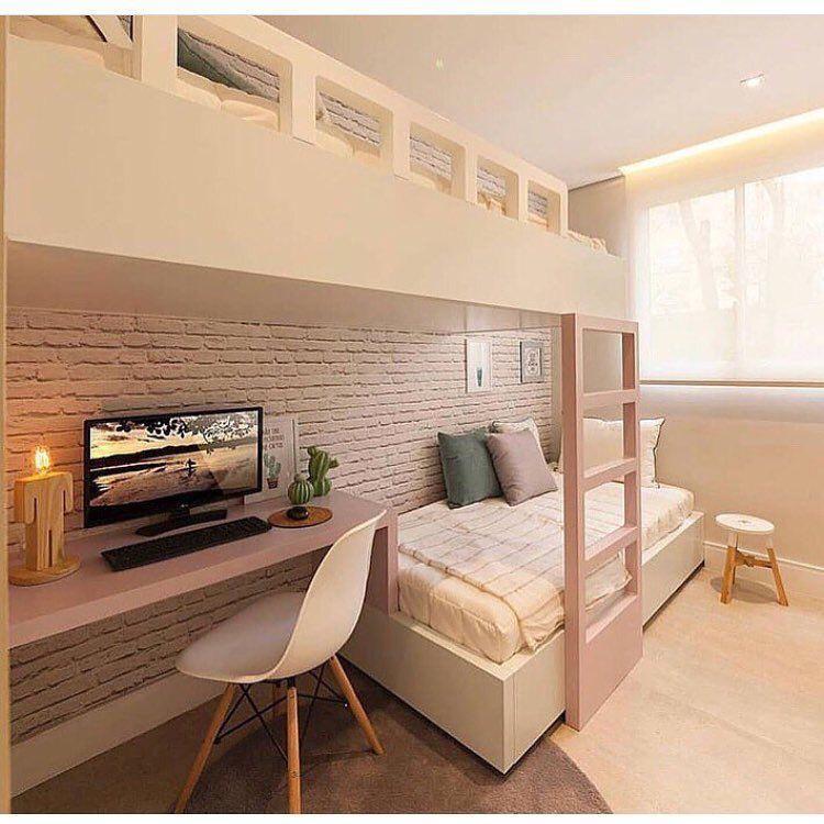 decoração para quartos pequenos com beliche branca e rosa, papel de parede de tijolinhos, escrivaninha rosa com cadeira branca e cadeira branca e piso de madeira.