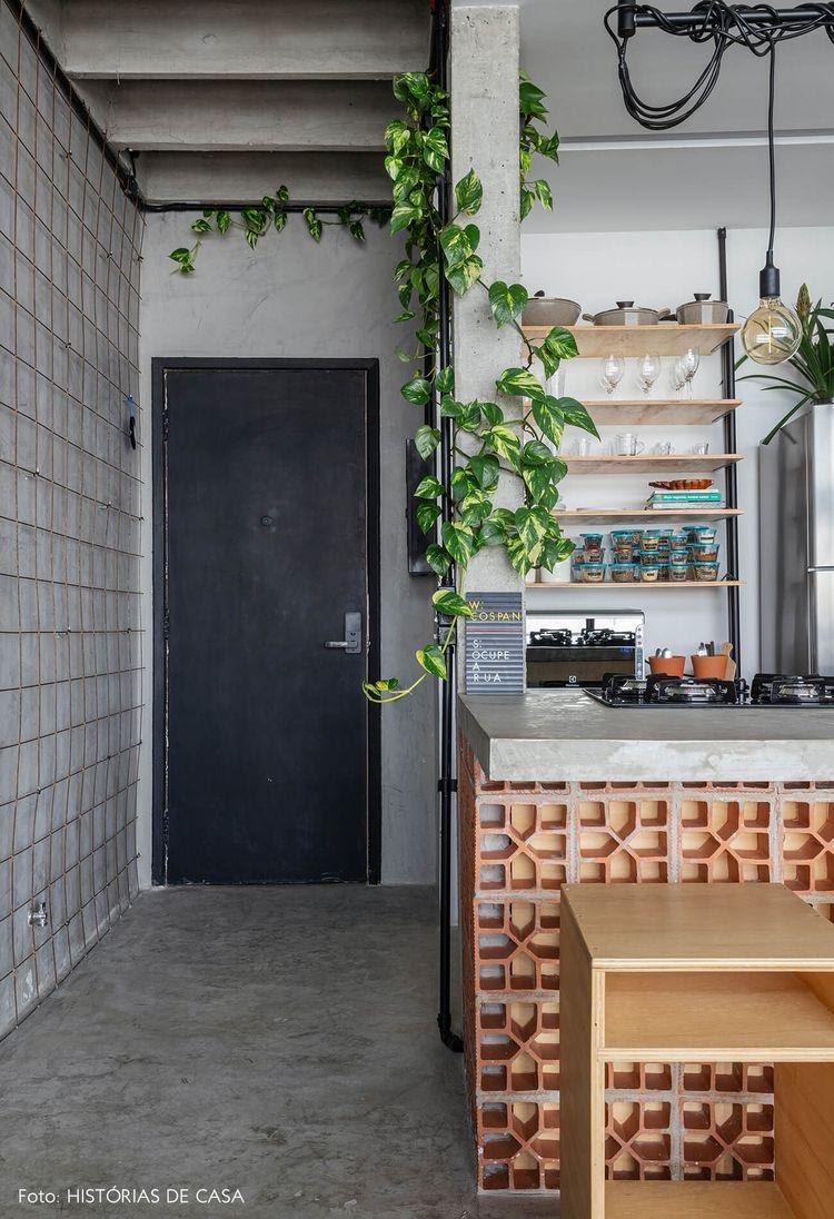 Apartamento estilo industrial, revestido de cimento queimado, com plantas na decoração e cobogo