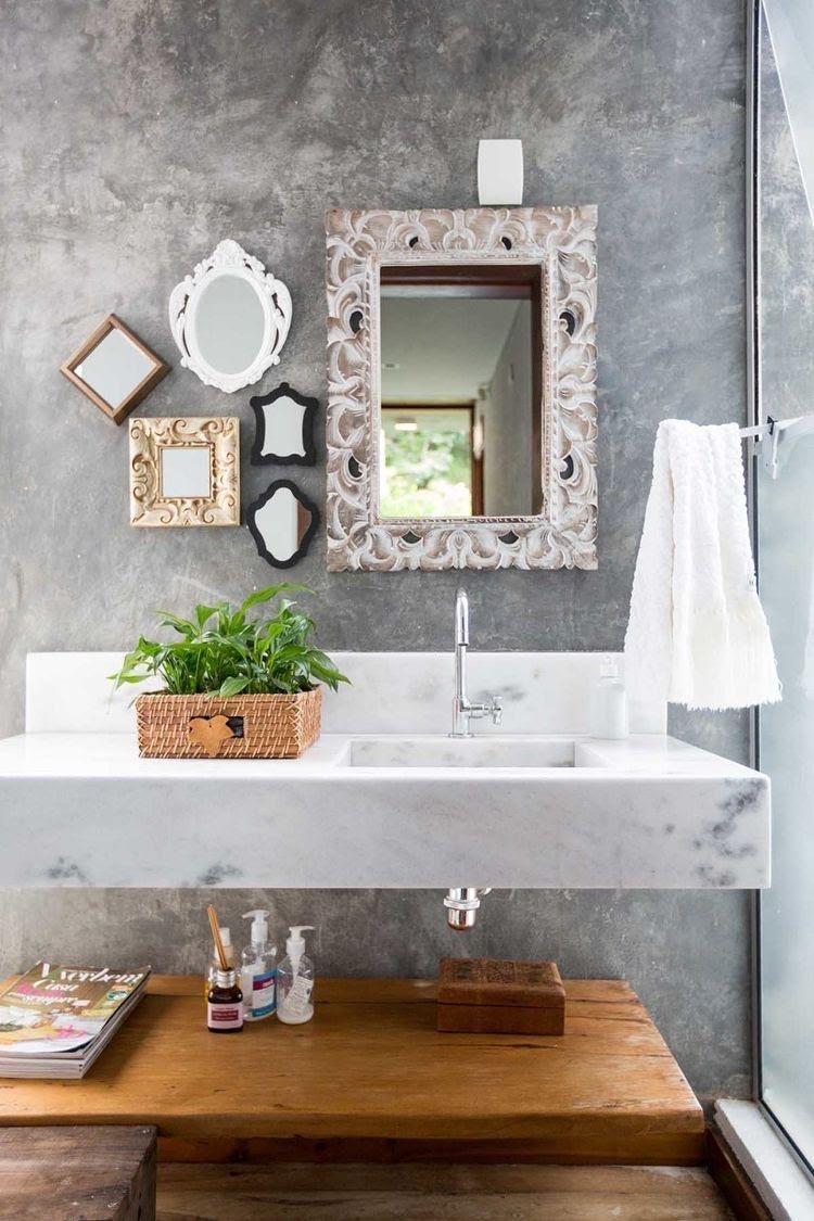 Banheiro com parede revestida de cimento queimado, espelhos na decoração, plantas e madeira