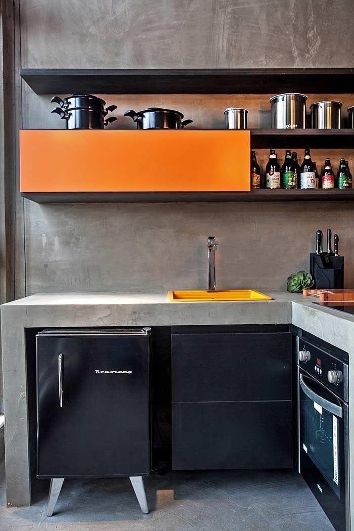 Cozinha com bancada e parede revestida de cimento queimado. Eletrodomésticos na cor preta. Pia amarela