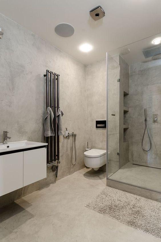 Banheiro amplo moderno, todo revestido de cimento queimado, box de vidro, pia e vaso sanitário brancos