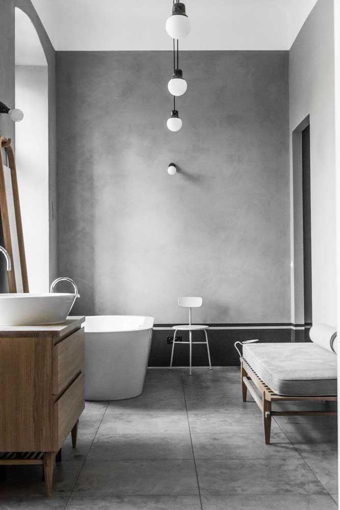 Banheiro moderno todo revestido de cimento queimado, detalhes em madeira. Banheira
