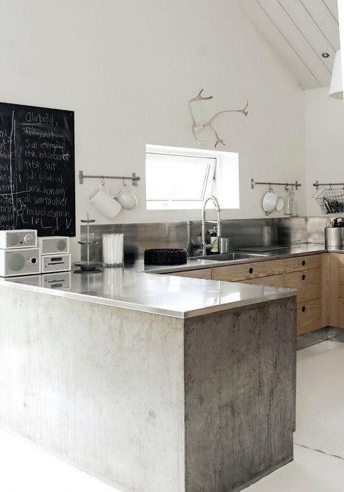 Cozinha moderna, com bancada revestida de cimento queimado, em estilo industrial. Detalhes em madeira nos armários