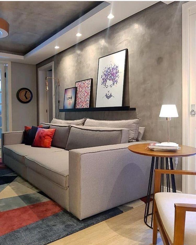 Sala de estar com parede revestida de cimento queimado, piso laminado, sofá cinza, detalhes de madeira, abajur