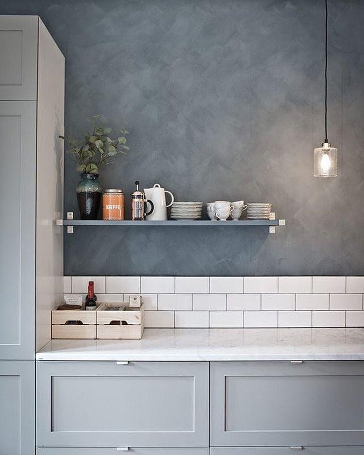 Ambiente com parede revestida de cimento queimado, balcão cinza, luminária pendente, azulejos brancos