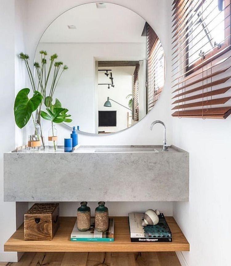 Lavabo com pia revestida de cimento queimado, detalhes de madeira, plantas na decoração, chão de madeira