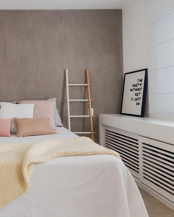 Quarto com parede revestida de cimento queimado, escada de madeira, quadro, armário branco