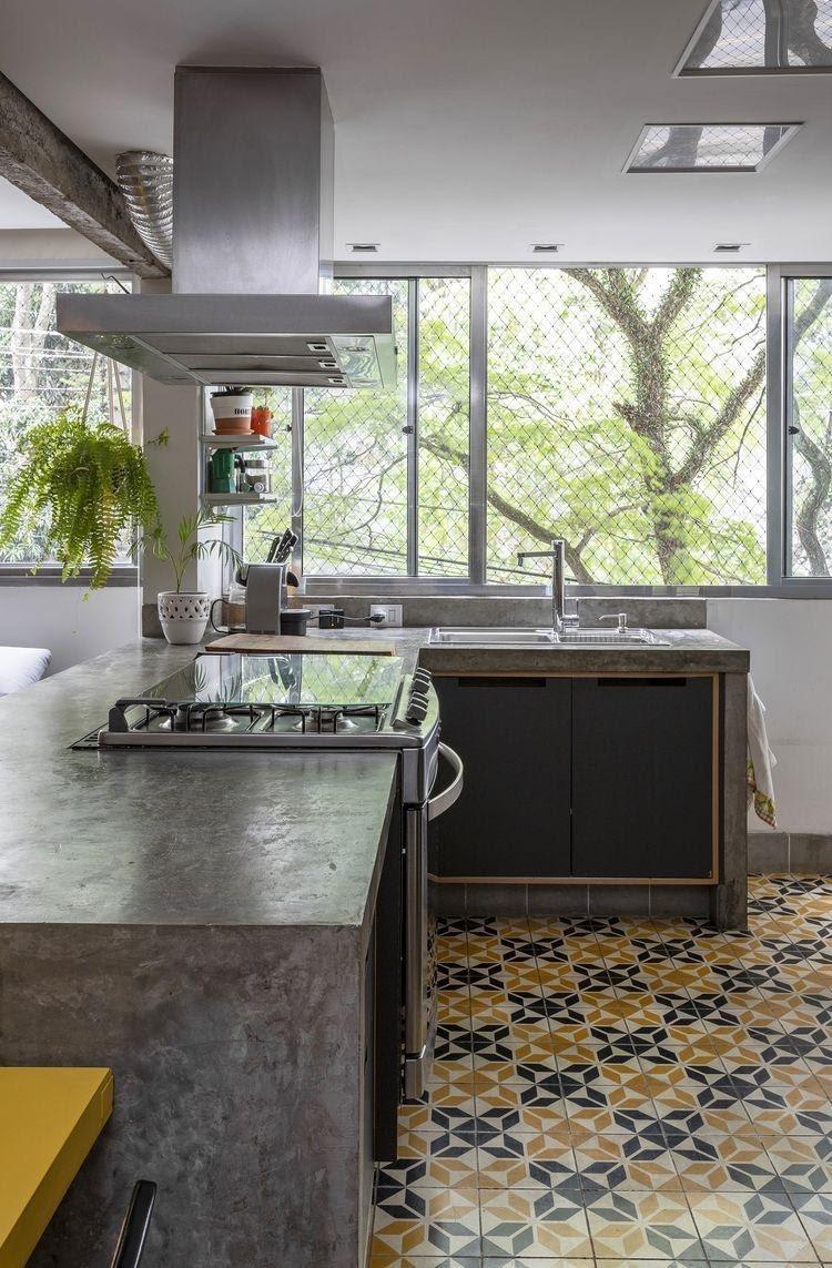 Cozinha revestida com cimento queimado na bancada e piso com ladrilhos preto e amarelo