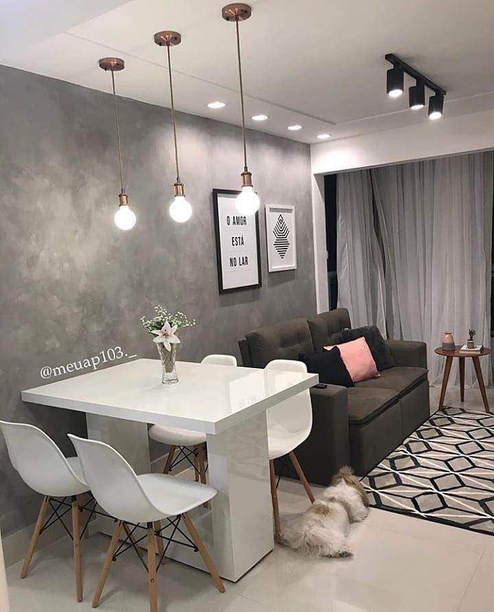 Sala de estar pequena, estilo moderno, parede revestida em cimento queimado e luminárias pendentes na decoração