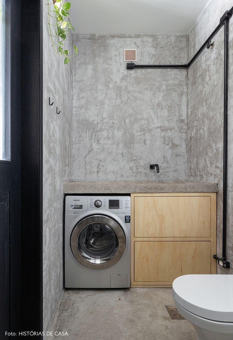 Lavanderia estilo industrial, revestida com cimento queimado e armário embutido
