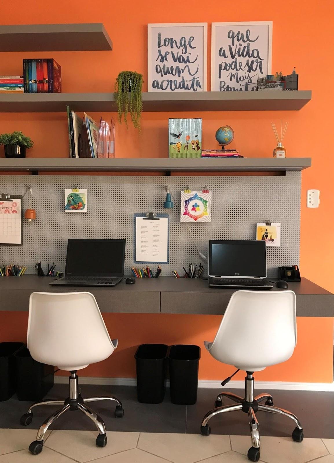 Ambiente de home office com chapa perfurada, computadores, cadeiras e quadros.