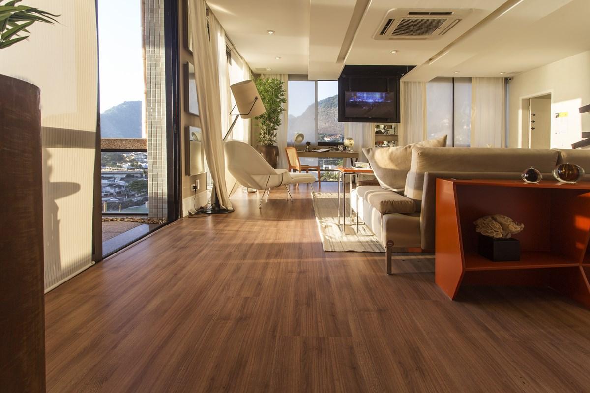Sala com piso laminado, televisão, sofá e poltronas brancos e plantas decorativas.