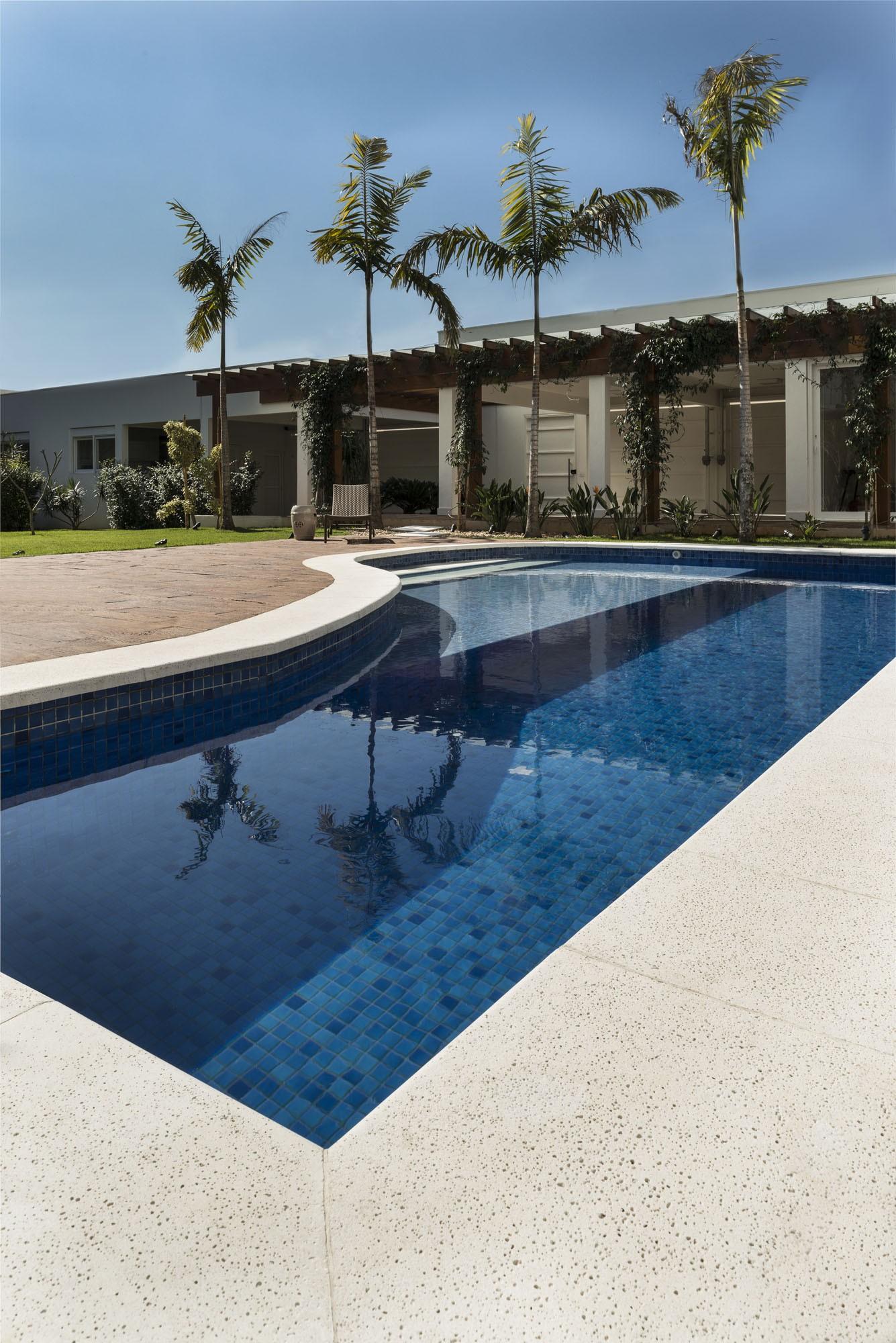 Ambiente com palmeiras, plantas e piscina com borda de cimentício.