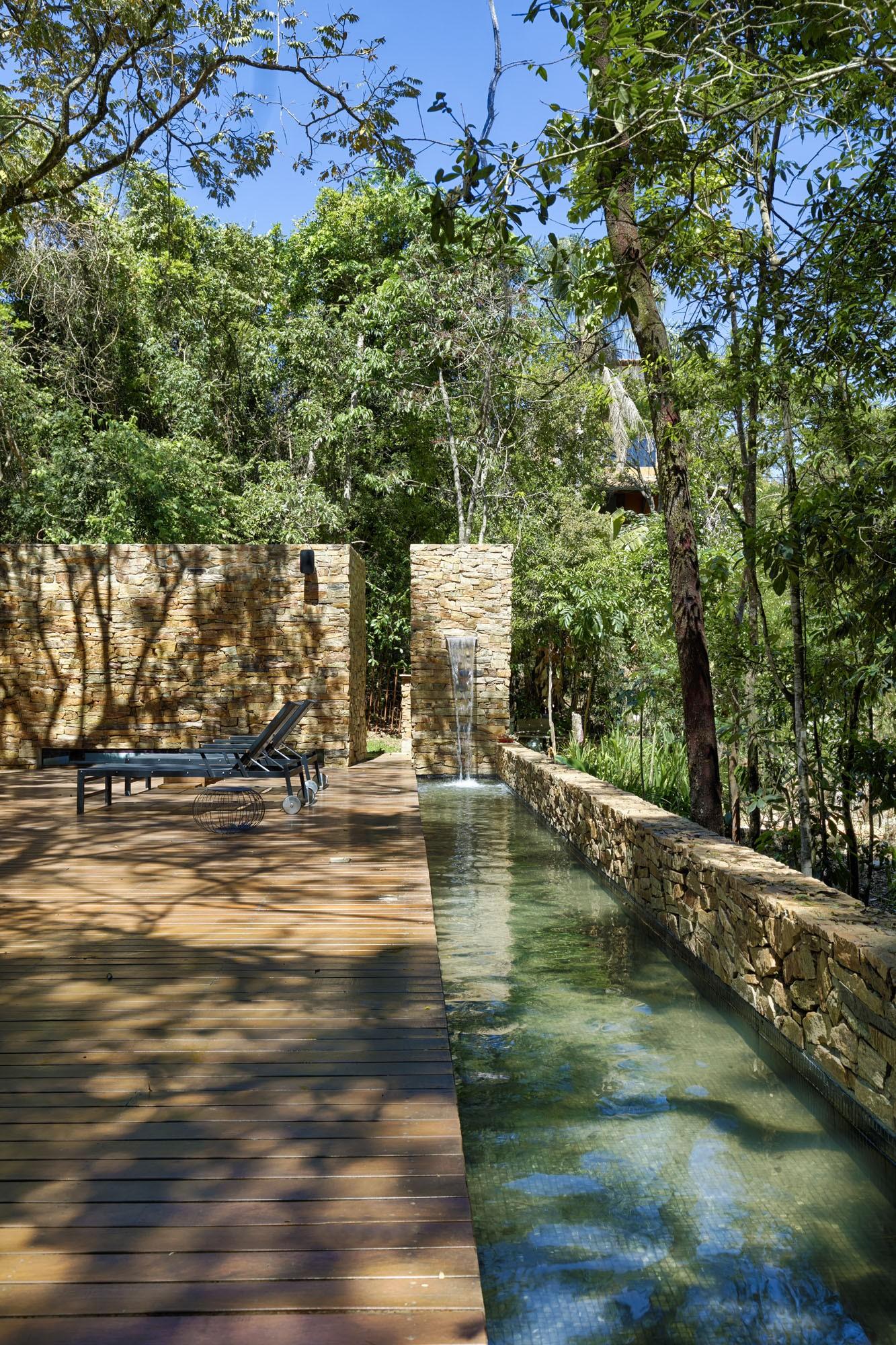 Ambiente com árvores, piscina com borda de pedra natural e deck de madeira