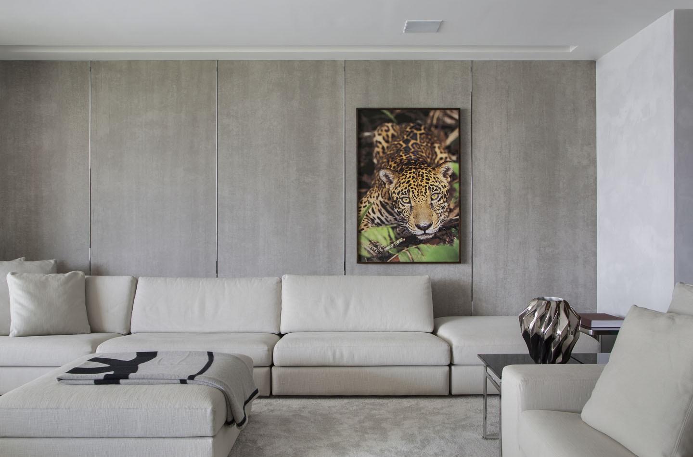 Sala com sofá branco, quadro com imagem de um tigre e parede de drywall.