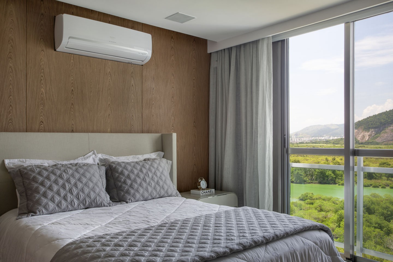 Quarto de casal com ar condicionado, porta de vidro e parede de drywall.