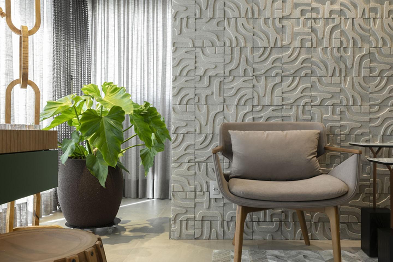 Ambiente com poltrona, vaso de planta e parede de drywall.