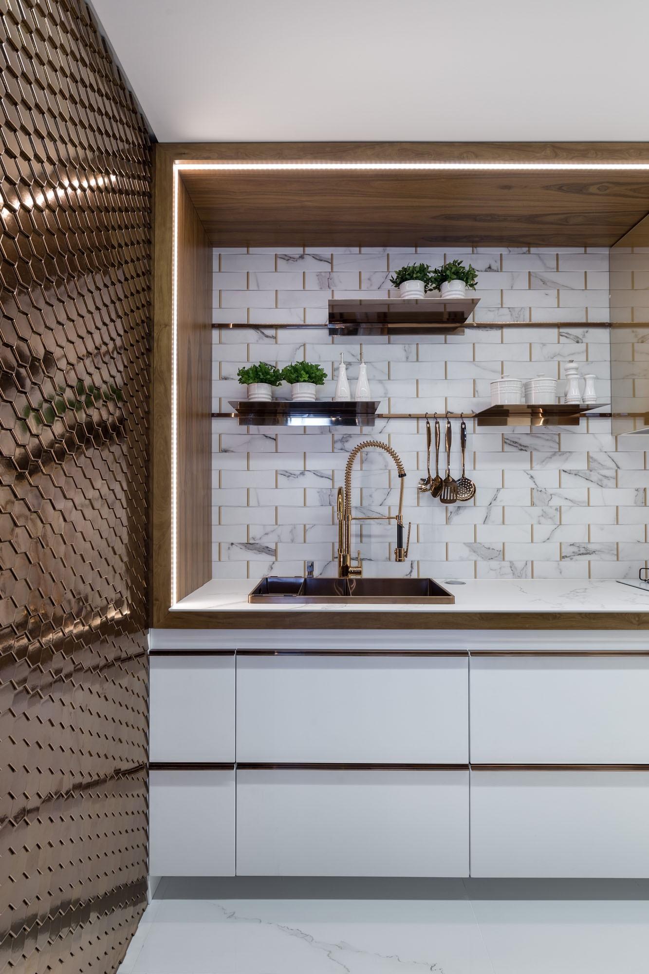 Cozinha com torneira dourada, pia branca, acessórios e parede de drywall.