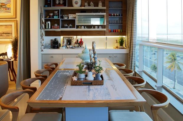 Envidraçamento de sacada rústica, com armário de madeira com utensílios, mesa de madeira e vasos decorativos.