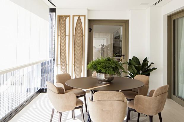 Sacada envidraçada com mesa redonda com cadeiras e planta decorativas.