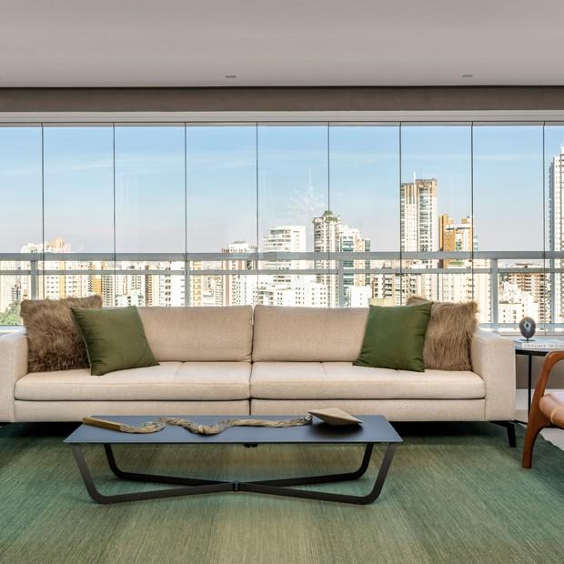 Sacada envidraçada com estilo clean, sofá branco com almofadas coloridas, tapete verde e mesinha de centro preta.
