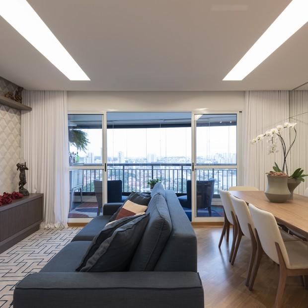 Sala de apartamento  com sofá cinza com mesa de jantar de madeira com vista para sacada envidraçada