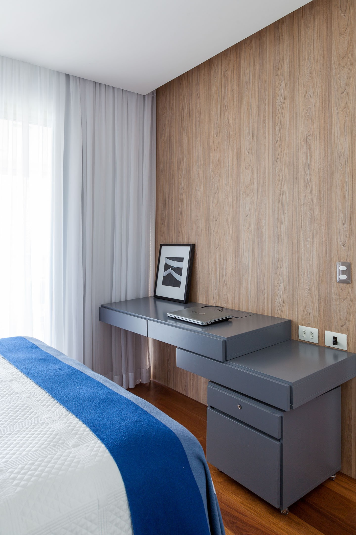 Quarto com piso amadeirado e revestimento de madeira nas paredes.