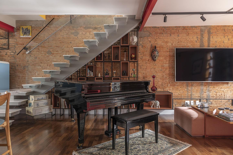 Sala com piso de madeira, piano de cauda e escada.