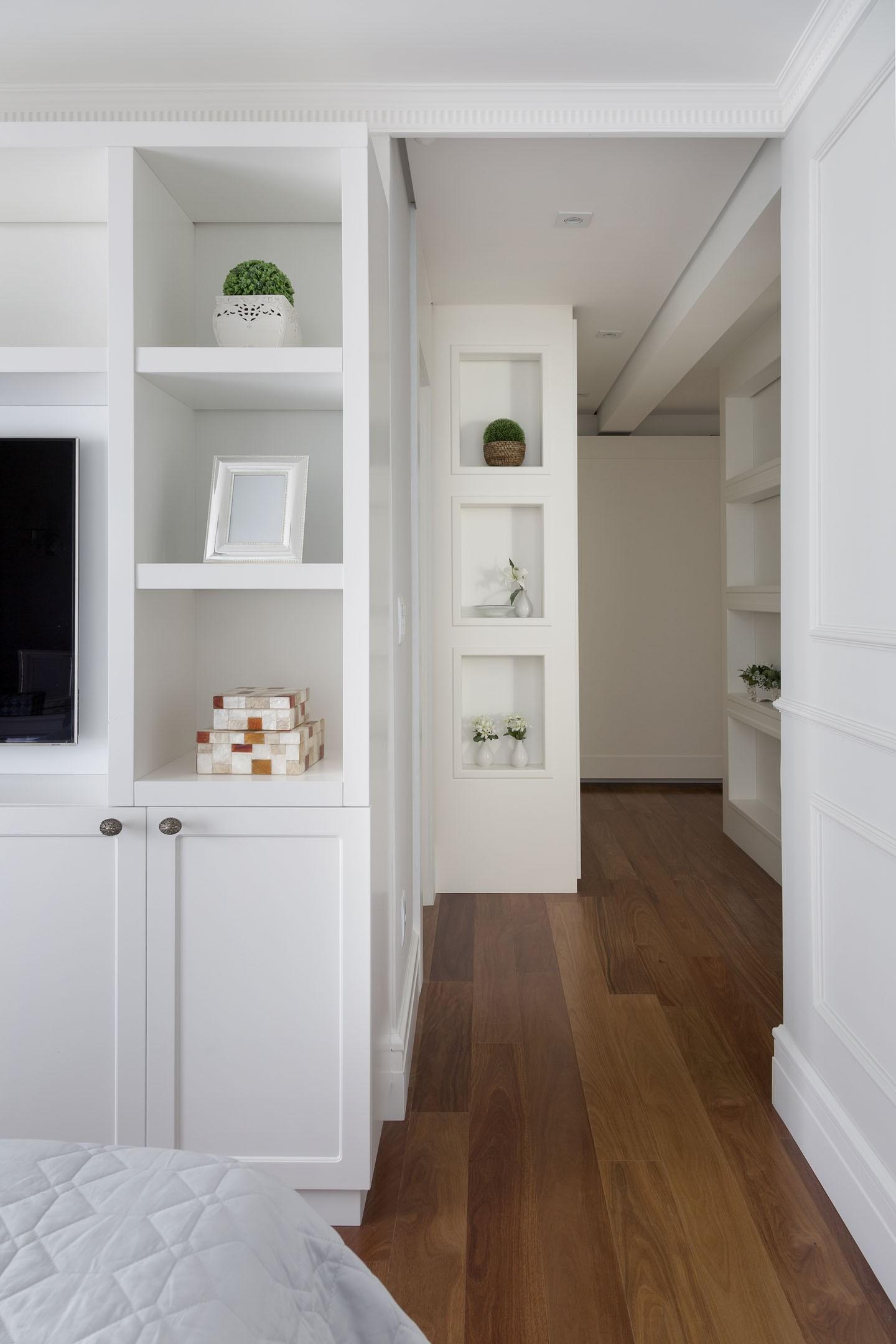 Quarto com armário branco e piso de madeira.
