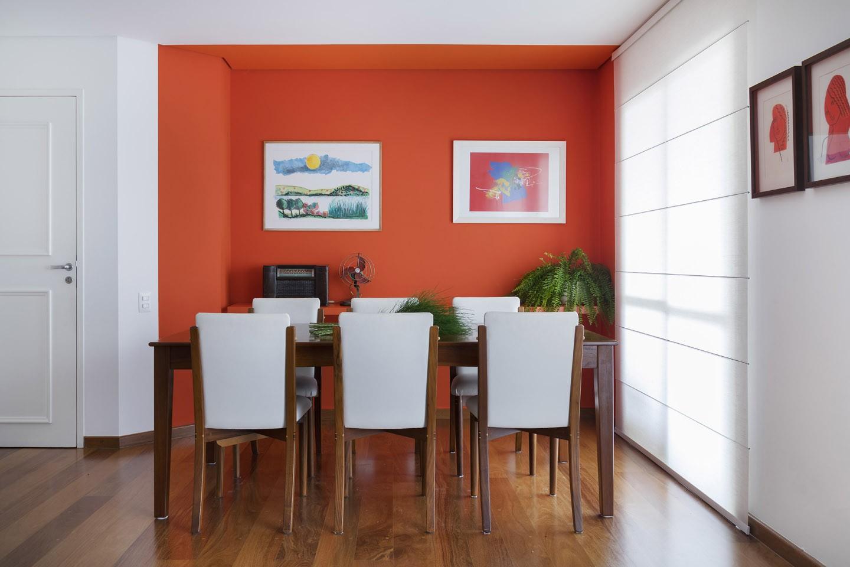 Ambiente com parede laranja, piso de madeira e mesa com cadeiras.