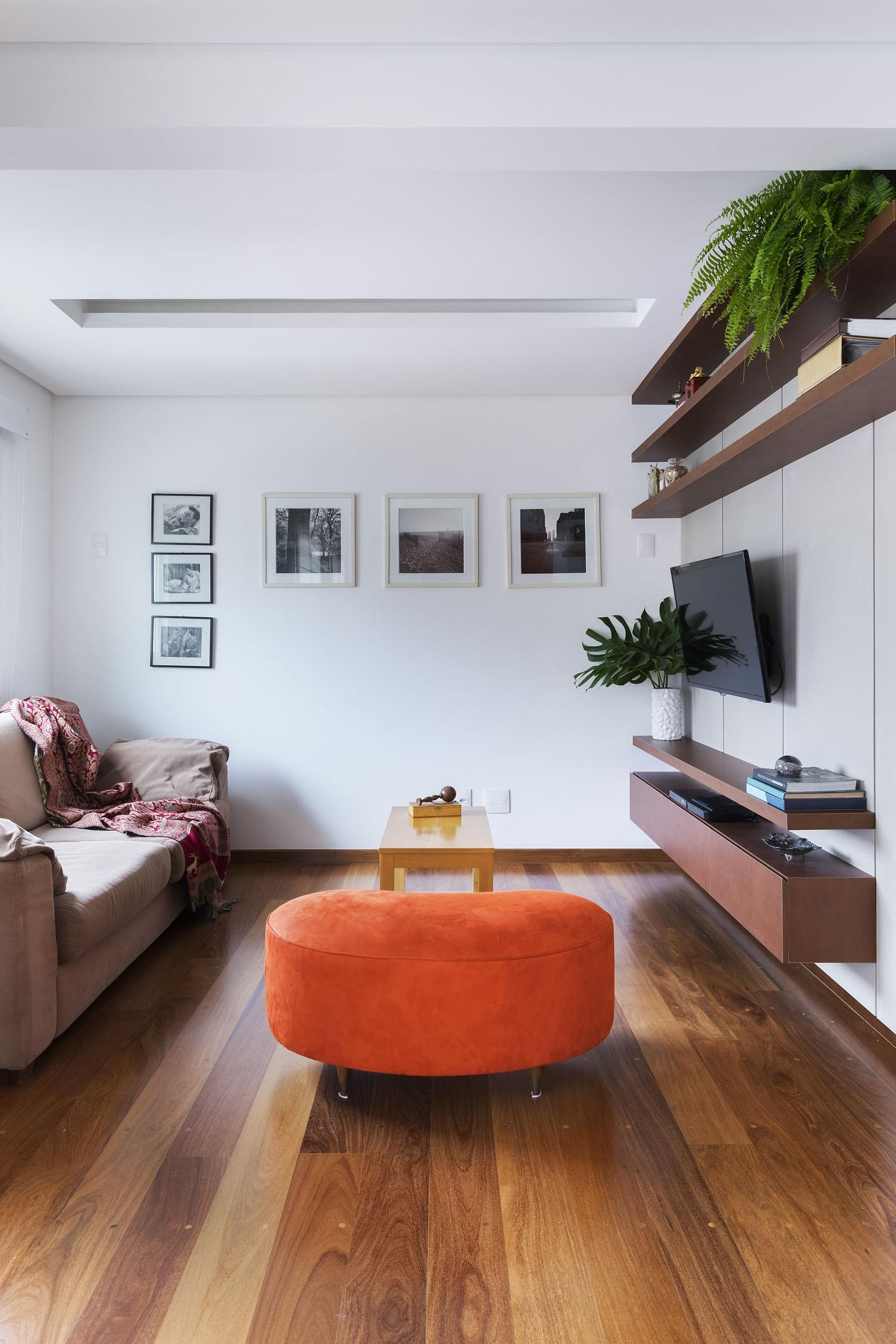 Sala com TV, sofá, puff decorativo e piso de madeira.