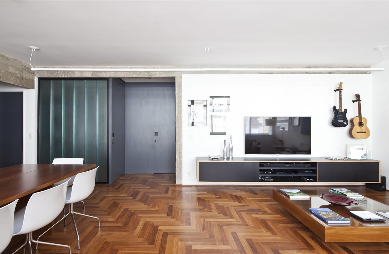 Sala com piso de madeira,mesa com cadeiras, televisão e violão na parede.