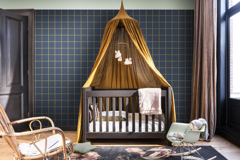 Quarto de bebê com berço e dossel de teto, cadeiras de balanço e parede pintada para uma obra econômica.