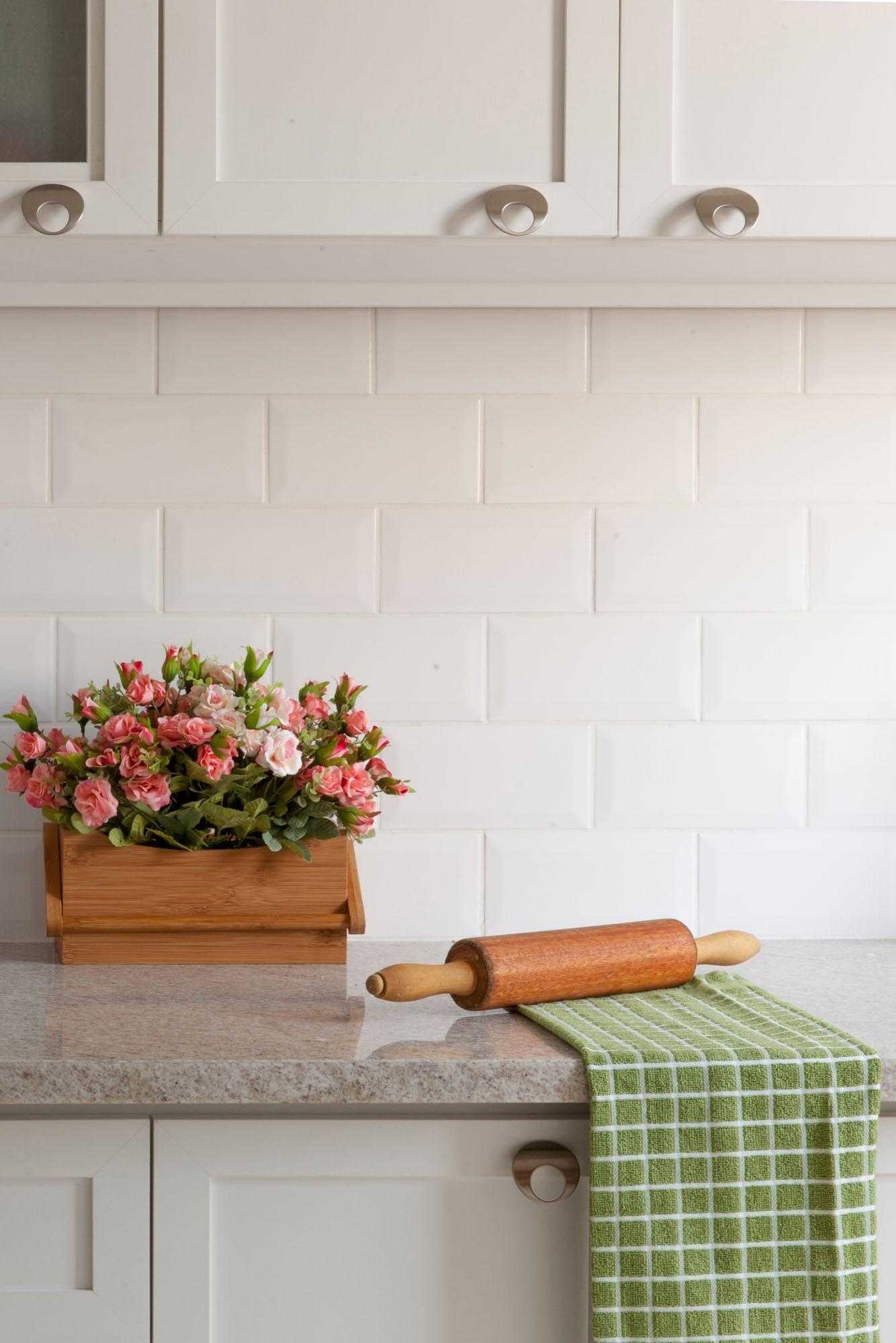 Bancada com revestimento de mármore, rolo de massa, vaso de flor e azulejo metrô branco.