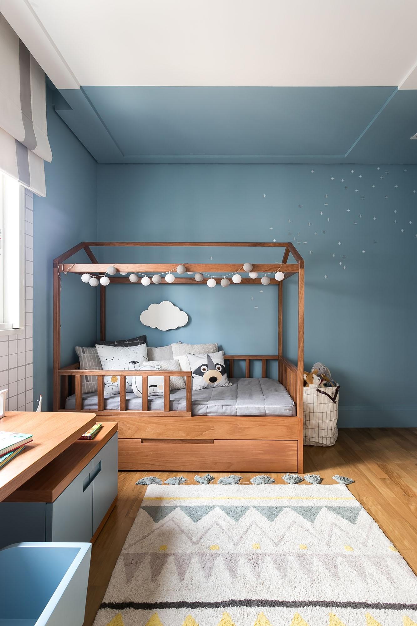 Quarto de criança com bicama, piso de madeira e papel de parede azul para uma obra econômica.