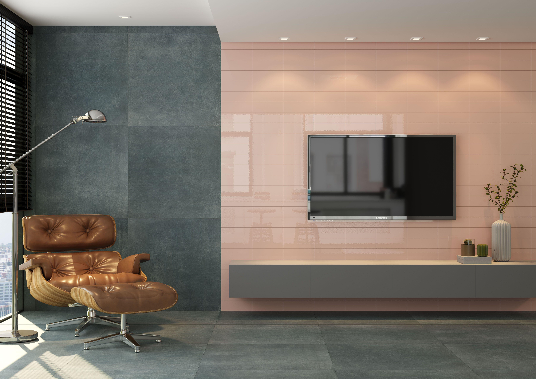 Ambiente com revestimento rose na parede de painel da TV, poltrona marrom e piso cinza.