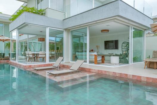 Área externa de casa com piscina e espreguiçadeiras.