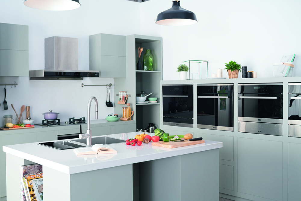 Cozinha branca com cuba e demais acessório de inox e bancada de porcelanato.