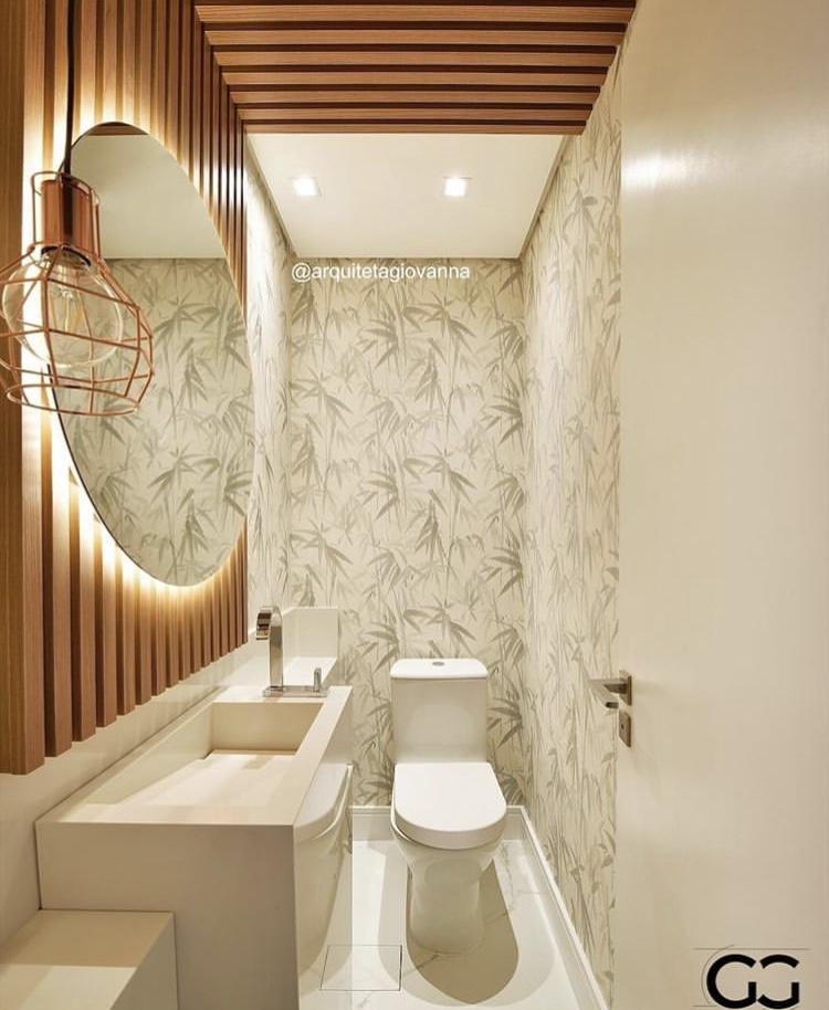 Banheiro com revestimento de folhas de planta na parede, iluminação solar e acessórios brancos.