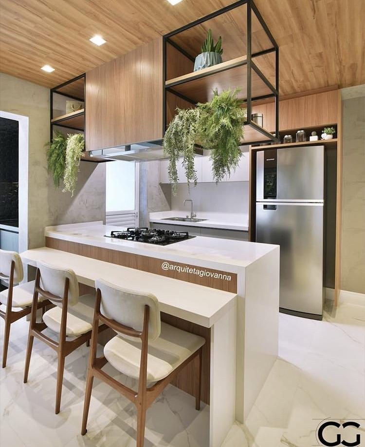 Cozinha com revestimento de madeira no teto, bancada e piso de porcelanato com plantas e iluminação solar.