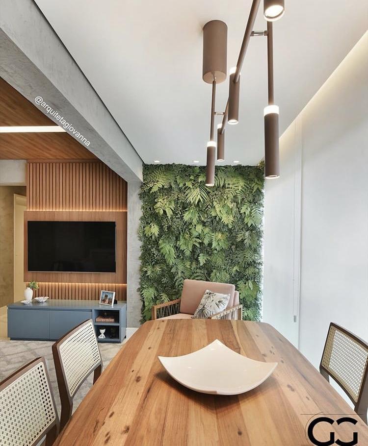 Ambiente com jardim vertical, mesa de madeira, iluminação solar.