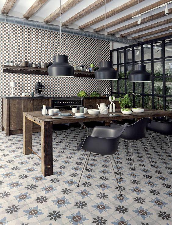 Area gourmet com ladrilhos no piso e na parede, mesa de madeira com cadeiras pretas, armários e prateleiras de madeira e lâmpadas pendentes pretas.